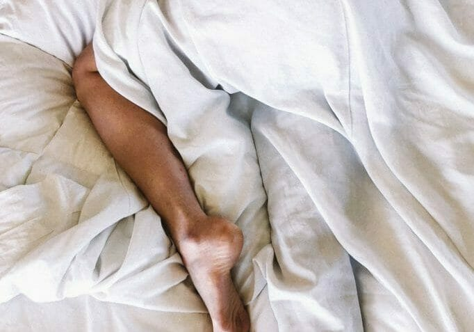 a rumpled bed with a visible foot, after a hookup