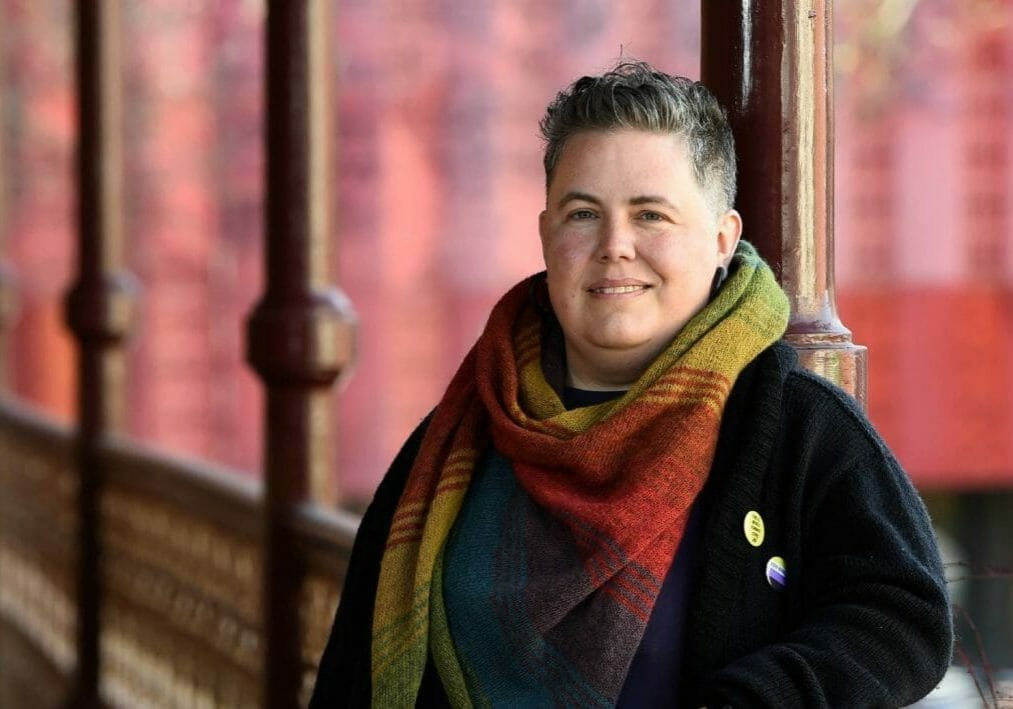 alex bayley - transgender advocate - standing against a fence wearing a rainbow scarf